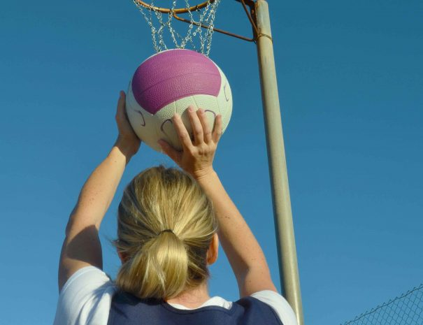 A woman shoots a netball goal